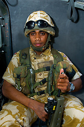 """TEX, a British soldier from the Duke of Wellington's Regiment wearing desert camouflage, Kevlar Helmet and body armor, carrying an SA80 assault rifle fitted with SUSAT sight, travels in the back of an armored Land Rover also known as a """"Snatch"""" during a patrol on Op-Telic in March 2005."""
