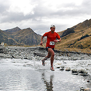 Runner Adam Keen crosses Moke Creek on the Ben Lomond High Country Station during the Pure South Shotover Moonlight Mountain Marathon and trail runs. Moke Lake, Queenstown, New Zealand. 4th February 2012. Photo Tim Clayton