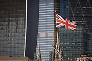 Seen from the south bank of the river Thames, a Union Jack flag flies on the bow of WW2 battleship HMS Belfast with the City of London - the capitals financial centre aka The Square Mile in the background, on 27th September 2018, in London, England.