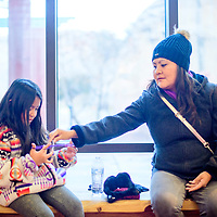 Candice Kelwood, right, helps Mackenzie Johnson with a traditional string game before the start of the Winter Stories tour at the Navajo Nation Zoo in Window Rock Wednesday.