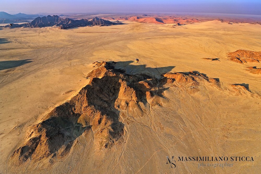 """The Namib is a coastal desert in southern Africa. The name Namib is of Nama origin and means """"vast place"""". According to the broadest definition, the Namib stretches for more than 2,000 kilometres (1,200 mi) along the Atlantic coasts of Angola, Namibia, and South Africa, extending southward from the Carunjamba River in Angola, through Namibia and to the Olifants River in Western Cape, South Africa. The Namib's northernmost portion, which extends 450 kilometres (280 mi) from the Angola-Namibia border, is known as Moçâmedes Desert, while its southern portion approaches the neighboring Kalahari Desert. From the Atlantic coast eastward, the Namib gradually ascends in elevation, reaching up to 200 kilometres (120 mi) inland to the foot of the Great Escarpment. Annual precipitation ranges from 2 millimetres (0.079 in) in the most arid regions to 200 millimetres (7.9 in) at the escarpment, making the Namib the only true desert in southern Africa. Having endured arid or semi-arid conditions for"""