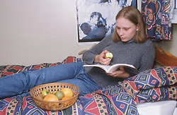 Teenage girl lying on bed in bedroom eating apple and reading book,