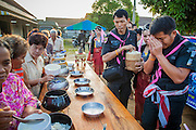 31 OCTOBER 2012 - YARANG, PATTANI, THAILAND:  Officers in the Thai Army make merit by donating food to Wat Kohwai at a special Tak Bat before escorting villagers on a procession to Yala for Ok Phansa. Ok Phansa marks the end of the Buddhist 'Lent' and falls on the full moon of the eleventh lunar month (October). It's a day of joyful celebration and merit-making. For the members of Wat Kohwai, in Yarang District of Pattani, it was a even more special because it was the first time in eight years they've been able to celebrate Ok Phansa. The Buddhist community is surrounded by Muslim villages and it's been too dangerous to hold the boisterous celebration because of the Muslim insurgency that is very active in this area. This the year the Thai army sent a special group of soldiers to secure the village and accompany the villagers on their procession to Yala, a city  about 20 miles away.  PHOTO BY JACK KURTZ