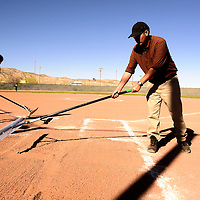 032715  Adron Gardner/Independent<br /> <br /> Roshawn white, left, and Zachary Emerson rake the batter's box before the start of the Navajo Pine Warriors and Thoreau Hawks game in Tohatchi Friday.