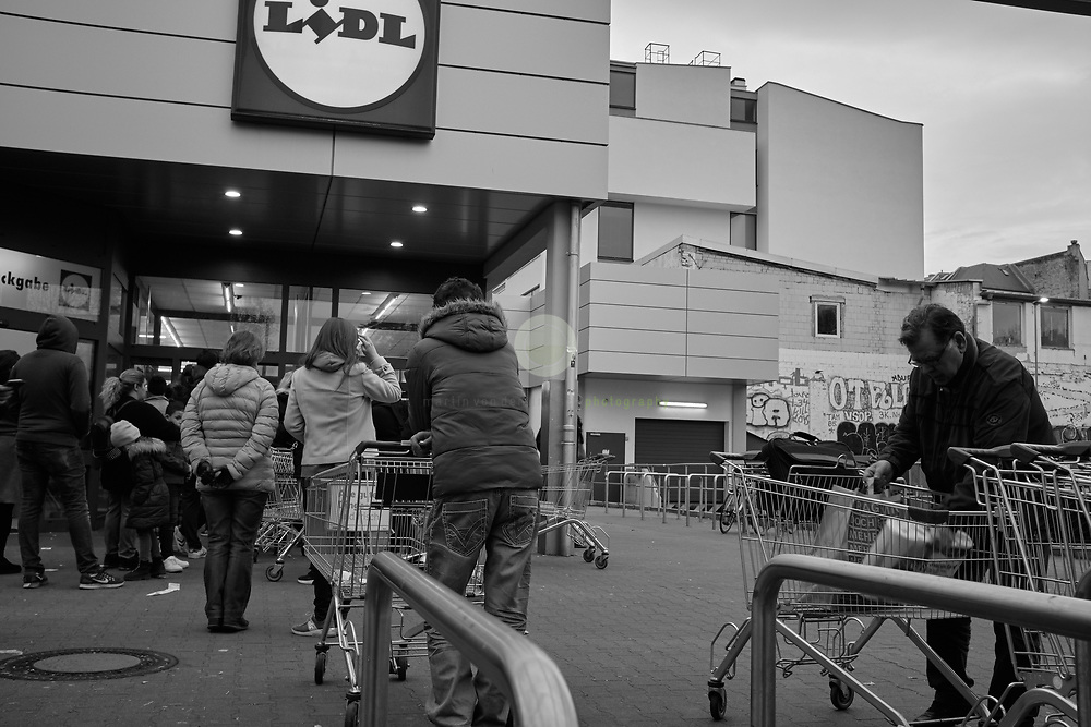 DEUTSCHLAND, Berlin, Wedding, 20.03.2020. Coronavirus-Pandemie: Social Distancing bei Lidl: Ein Schild weist darauf hin, dass sich aufgrund von Covid-19 maximal 70 Kunden im Laden aufhalten duerfen. Ein Wachmann kontrolliert den Einlass.<br /> <br /> Schwarz-Weiss (Original in Farbe).
