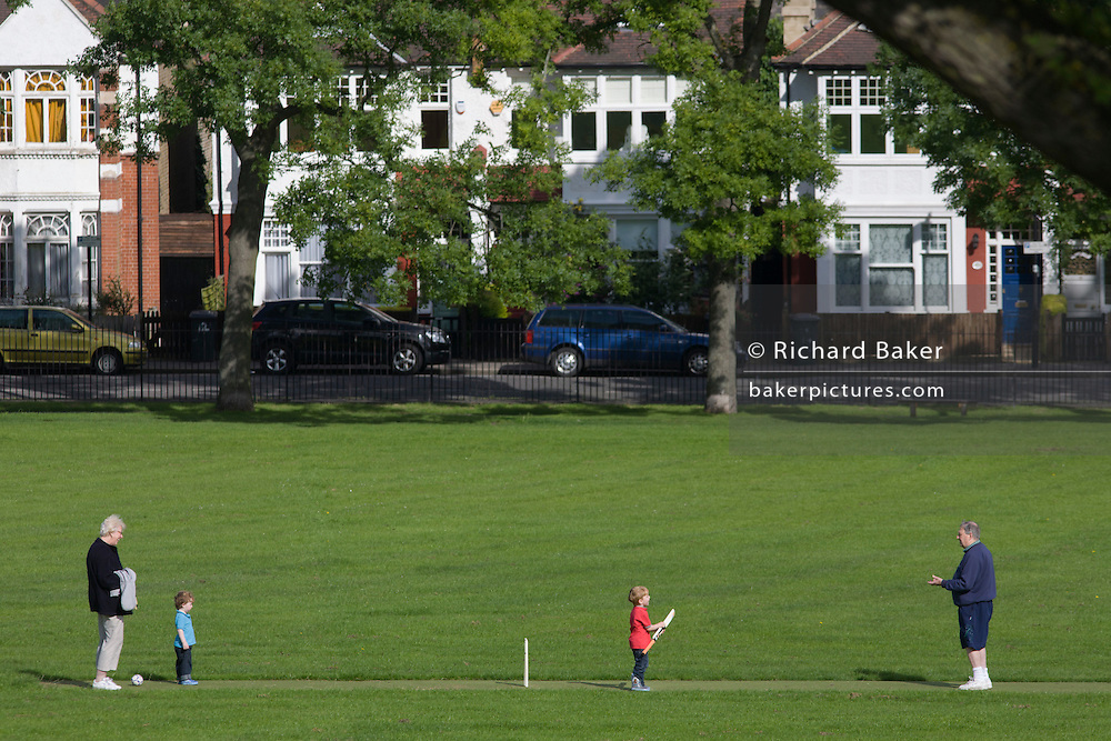 Grandparents look after their two young grandchildren with cricket games in a public park.