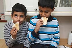 Asian boys eating toast.