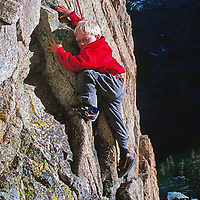 A youngster rock climbs on a crag in John Muir Wilderness.