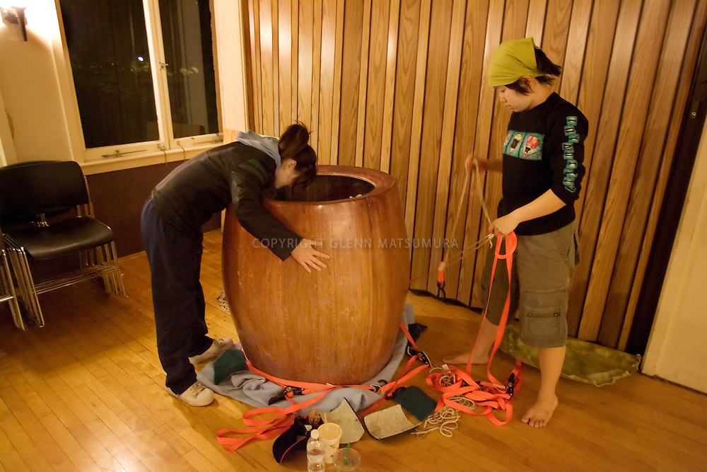 Stanford after dark. Rina Chang (2007) checks the taiko drum before packing. Michelle Kwon (2007) readies the packing straps