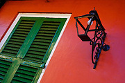 Green shutters and a wrought iron light against a red building in the French Quarter in New Orleans, Louisiana.