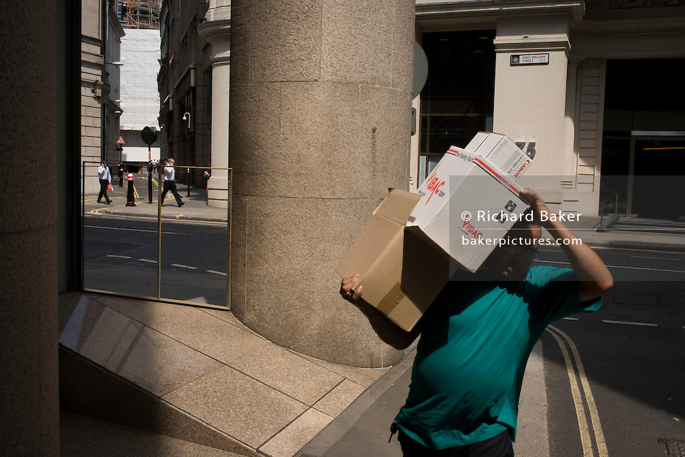 A courier delivers boxes on his shoulder along a narrow side street at the junction of King William Street in the City of London, the capital's Square Mile, and its financial heart.