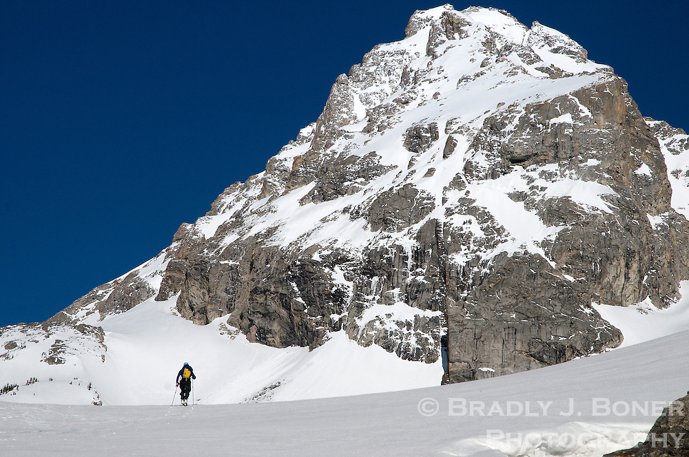 Dwarfed by the Middle Teton, Kevin Olson enters The Meadows in Garnet Canyon during a spring ski tour in Grand Teton National Park.