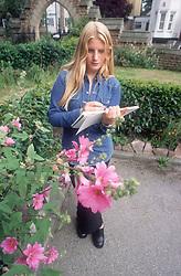 Teenage girl standing in park drawing flower,