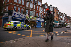 © Licensed to London News Pictures. 05/01/2021. London, UK. A woman wearing a protective face covering in north London as England begins its third national lockdown. Prime Minister Boris Johnson announced on Monday 4 January 2021 that England goes into third national lockdown until at least 22 February 2021, with households ordered to stay home and only go outside for the specific reasons. Photo credit: Dinendra Haria/LNP