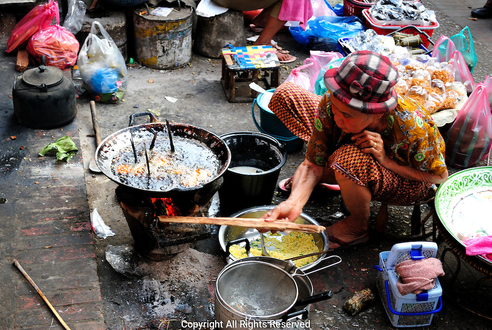 Woman cooking snacks to sell at the food market.