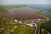 """Nederland, Noord-Holland, Gemeente Amsterdam, 28-04-2010; recreatieterreinen aan de IJsselmeerdijk of Uitdammerdijk en het Kinselmeer, tussen Durgerdam en Uitdam (aan de horizon), camping 'De Badhoeve' in de voorgrond, op het schiereilandje in het midden aan de dijk komt een nieuw recreatieterrein, 'Ecopark Kinselmeer'. Het meer is oorspronkelijk ontstaan bij de dijkdoorbraak van de Waterlandse zeedijk in 1570 (de  Allerheiligenvloed) en bij volgende doorbraken, onder andere de watersnood van 1825,  steeds verder vergroot..Recreation grounds at Kinselmeer lake, between Durgerdam and Uitdam..On the small peninsula in the middle of the dike is a new recreational area,"""" Ecopark Kinselmeer """". The lake originates from the 1570 dike breach of the Waterland seawall (former Zuyder Zee dike). Subsequent breakthroughs, including the flood of 1825, have enalrged the lake..luchtfoto (toeslag), aerial photo (additional fee required).foto/photo Siebe Swart"""