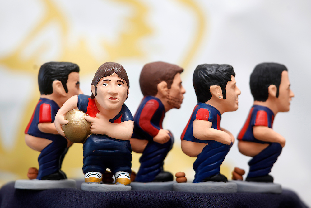 """November 10,  2010. A company in Torroella de Montgrí (Girona, Spain) called """"Caganer.com"""", which specializes in the production of """"caganers"""", unveiled today its new figurine for Christmas, Michael Jackson, Josn Lennon or prince Charles. .A """"Caganer"""" is a small figure from Catalonia, usually made of fired clay, which depicts as squatting person in the act defecating..""""Caganer"""" is Catalan for pooper. It forms part of one of the typical figures of the manger or """"Nativity"""" scene together with Mary, Joseph and the baby Jesus but hidden in a corner. It is a humorous figure, originally portraying a peasant wearing a """"barretina"""" (a red stocking hat), and seems to date from the 18th century when it was believed that the figure's deposits would fertilize the earth to bring a prosperous year. With the course of time, the original personage of this pooping figure was substituted with personalities from the political and sports worlds and other famous personalities..F.C. Barcelona footlball team. From left to right Pedro, Messi (with the Golden Ball FIFA won last year), Gerard Pique, David Villa and Busquets."""