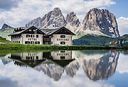 A pond reflects Hotel Gonzaga and peaks of the Langkofel Group (Sassolungo, 3181 meters / 10,436 feet) and Sella Group, in Val di Fassa, 2 km west of Passo Pordoi, in the Dolomites, Trentino-Alto Adige/Südtirol region, Italy. We highly recommend lodging in a pristine, roomy apartment with full kitchen in a beautiful setting at Hotel Gonzaga Appartamenti Garni (Canazei, I-38032, Streda de Pordoi, 102, telephone +39 0462 602121). The Dolomites are part of the Southern Limestone Alps, Europe. UNESCO honored the Dolomites as a natural World Heritage Site in 2009.