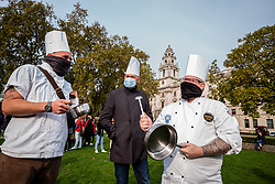 © Licensed to London News Pictures. 19/10/2020. London, UK. Three chefs bang saucepans with a spoon at a protest by hospitality workers in Parliament Square against tougher Covid restrictions and the amount of financial compensation given to the industry. Today, Wales's First Minister Mark Drakeford has announced a two week 'firebreaker' for Wales with shops, bars, pubs and cafes to closed and people ordered to stay at home from this Friday pilling pressure on Prime Minister Boris Johnson to follow suit in England as coronavirus levels of infections continue to escalate throughout the UK. Photo credit: Alex Lentati/LNP