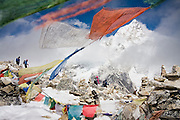 Trekkers hike past Buddhist prayer flags and rock cairns on Kala Patthar, for many the final destination on the Everest Base Camp Trek, Khumbu region, Sagarmatha National Park, Himalaya Mountains, Nepal. Nuptse (7861m) towers in the distance.