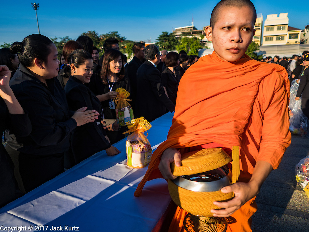 """20 JANUARY 2017 - BANGKOK, THAILAND: A Buddhist monk finishes his alms collecting during a """"tak bat"""" (alms giving ceremony) on the plaza in front of Bangkok's City Hall. Hundreds of municipal workers and civil servants made merit by praying and presenting alms to 89 Buddhist monks Friday to mark 100 days of mourning since the death of revered Bhumibol Adulyadej, the Late King of Thailand. The significance of 89 monks is that the King, who died on October 13, 2016, was a few weeks short of his 89th birthday.        PHOTO BY JACK KURTZ"""