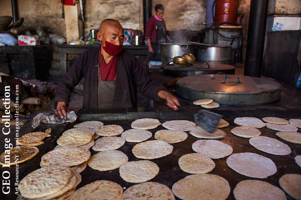 A monk in Gandze prepares the traditional flatbread of central Tibet, called balep korkun. It is cooked on a griddle and made with barley flour, water and baking powder. Sichuan, China