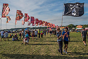The sun comes out at the end of the afternoon in the avenue of flags near the Other Stage - The 2017 Glastonbury Festival, Worthy Farm. Glastonbury, 2 June 2017