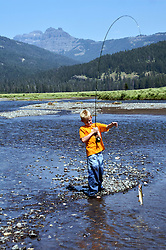 Boy landing cutthroat trout while Fly-fishing Soda Butte Creek in Yellowstone National Park.