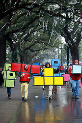 04 March 2014. New Orleans, Louisiana.<br /> Fat Tuesday. Mardi Gras Day.  Revelers in costume make their way along a cold and wet St Charles Avenue ahead of the parades as they walk downtown.<br /> Photo; Charlie Varley/varleypix.com