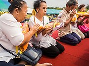 08 JANUARY 2015 - BANGKOK, THAILAND: Women pray and meditate in front of a large statue of a revered Buddhist monk at an altar on Sanam Luang in Bangkok. Buddhist in Bangkok have a chance to meditate in front of seven large statues of revered Buddhist monks and worship a hair relic of the Buddha at a series of altars on Sanam Luang near the Grand Palace in Bangkok.    PHOTO BY JACK KURTZ