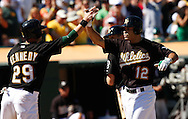 The Oakland Athletics' Scott Hairston (R) is congratulated by teammate Adam Kennedy following Hairston's seventh inning grand slam home run against the Seattle Mariners during their MLB American League baseball game in Oakland September 6, 2009.  REUTERS/Kevin Bartram (UNITED STATES)