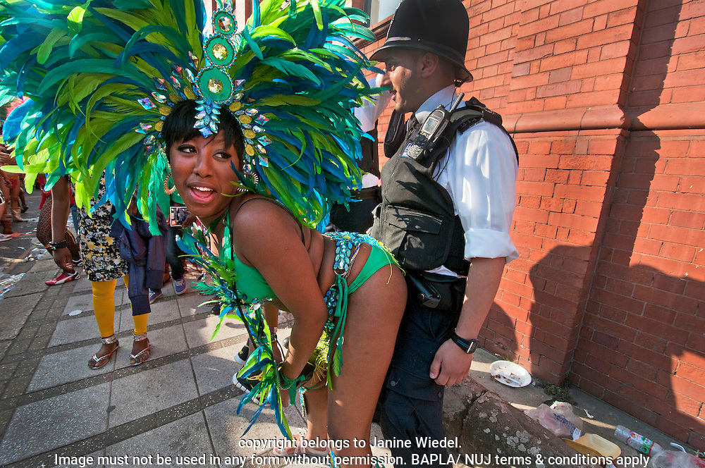 Policeman taking part in Notting Hill Carnival dancing with festival dancers