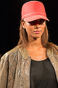 An orange cap, and patterened zipped jacket with tan leather shoulder and collar. By Monika Chiang at Spring 2013 Fashion Week in New York.