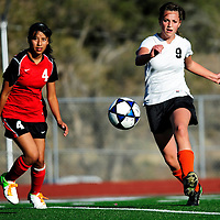 102412  Adron Gardner<br /> <br /> Gallup Bengal Taylor Wenning (9), right, launches a kick ahead of Grants Pirate Danielle Rael (4) at Public School Stadium Wednesday.