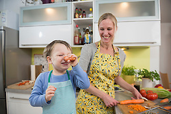 Boy fool around with carrots while mother is laughing