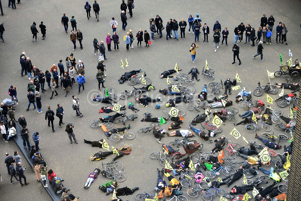 Tourists look on as cyclists from Extinction Rebellion stage a die in at Tate Modern called XR Critical Swarm on 27th April 2019 in London, England, United Kingdom. The action aims to highlight the global decline in the bee population and the sudden eradication of bee colonies known as Colony Collapse disorder. The climate change activist group are targeting the Tate who they claim, built their fortune on sugar cane production from colonial exploitation of enslaved Africans, European invasion and exploitation of land in West Indies and South America.