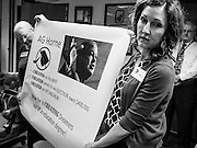 21 OCTOBER 2013 - PHOENIX, AZ: Protester MOLLY DURAN holds up a banner critical of Arizona Attorney General Tom Horne at a protest in the office of the AG in Phoenix. The DREAMers are protesting the decision by Attorney General Horne to sue the Maricopa County Community College District to force the district to charge in-state tuition to the young people who qualify for the federal government deferred-action program.    PHOTO BY JACK KURTZ