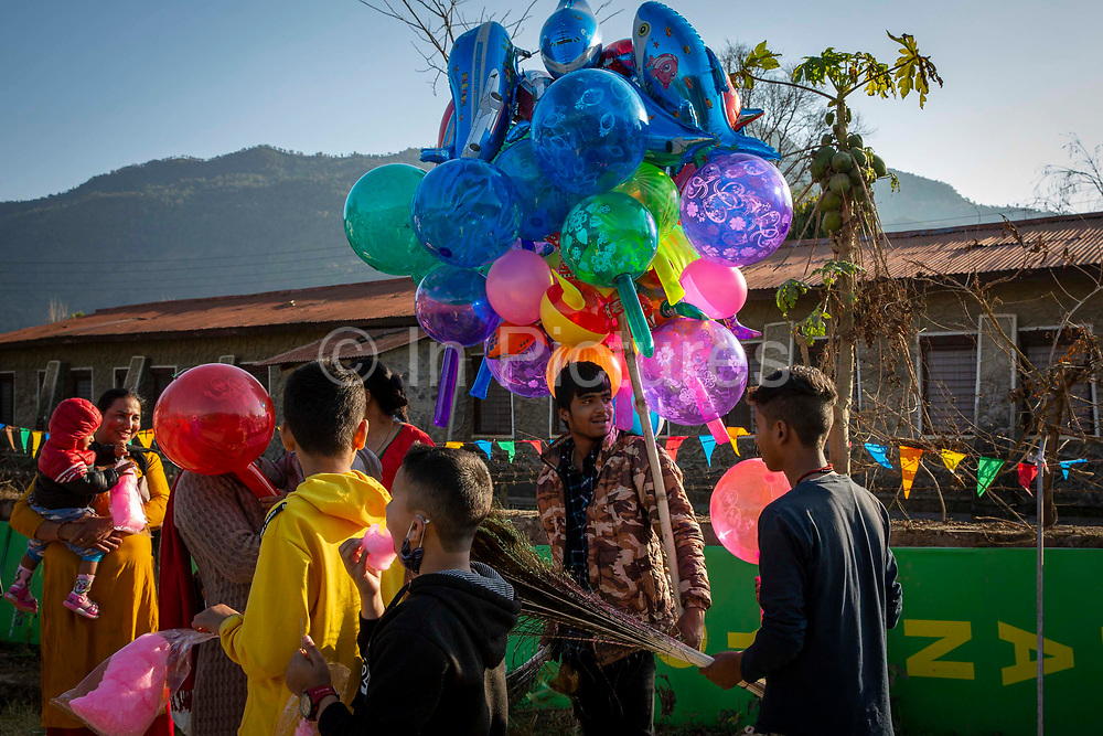 A teenage boy selling helium balloons outside a fairground on the 6th of March 2020 in Paudi, Sundarbazar, Lamjung District, Gandaki Pradesh, Nepal.  The fairground is part of the Holi celebrations, also known as Festival of Colours, is one of the most popular festivals in Nepal. It takes place on the full moon day in Nepali Fagu month (February to March in Solar Calendar) and lasts for 2 days.