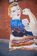 Glazed & Infused Maple Bacon Long John donut in front of the glazed mural in Wicker Park August 2, 2015 in Chicago, Illinois, USA.