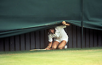 TENNIS - 1977 WIMBLEDON CHAMPIONSHIPS - ILIE NASTASE V JOHN ALEXANDER<br /> <br /> ILIE NASTASE OF ROMANIA, JOKES AROUND, HIDING UNDER THE CANOPY AT THE END OF THE COURT, IN BETWEEN GAMES DURING THE MATCH. <br /> <br /> CREDIT : COLORSPORT / ANDREW COWIE