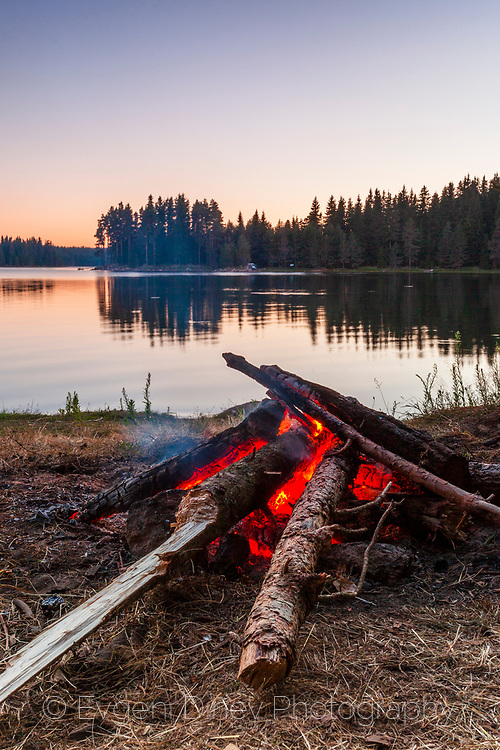 Fireplace by a mountain lake at dusk