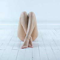 studio shot picture of a young beautiful breast naked  woman lying on a white floor flaping legs