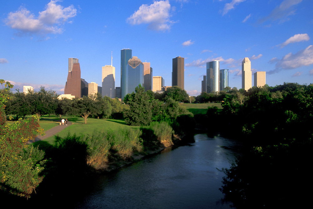 Couple with child and dog walking along Buffalo Bayou path with view of Houston, Texas skyline.