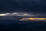 On a flight from Hong Kong to Jeju Island, early morning light shines in the distance as the plane descends into Jeju.
