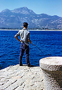 Man with fishing rod standing on quayside, Calvi, Corsica, France in late 1950s