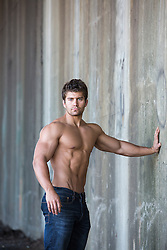 shirtless man in jeans leaning on a wall