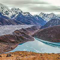 Trekkers climb a hill in the Gokyo Valley in the Khumbu region of Nepal's Himalaya. In the background are Cholatse and Taboche peaks, the Ngozumpa Glacier and Dudh Pokhari lake.