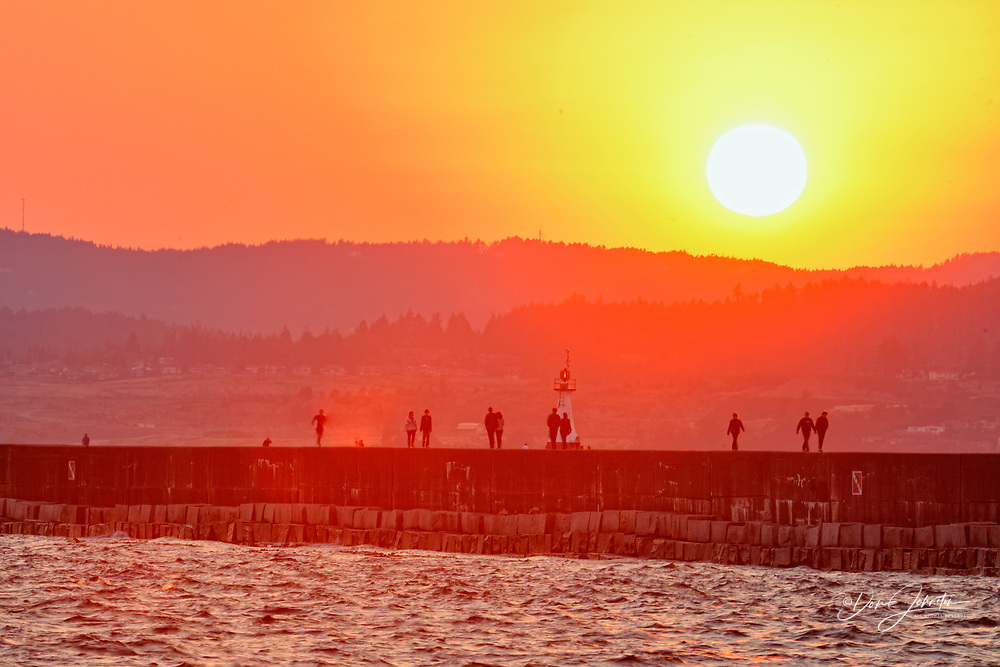 Breakwater wall with evening strollers at sunset, Victoria, British Columbia, Canada
