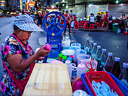 """18 MAY 2017 - BANGKOK, THAILAND: A dessert vendor makes a crushed ice dessert with coconut milk and sugar syrup on her mobile cart on Yaowarat Road in Bangkok. City officials in Bangkok have taken steps to rein in street food vendors. The steps were originally reported as a """"ban"""" on street food, but after an uproar in local and international news outlets, city officials said street food vendors wouldn't be banned but would be regulated, undergo health inspections and be restricted to certain hours on major streets. On Yaowarat Road, in the heart of Bangkok's touristy Chinatown, the city has closed some traffic lanes to facilitate the vendors. But in other parts of the city, the vendors have been moved off of major streets and sidewalks.      PHOTO BY JACK KURTZ"""