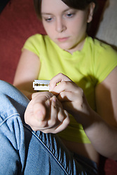 Young woman cutting herself with a razor blade,